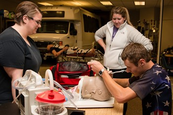 Two students and an instructor in the EMS lab.
