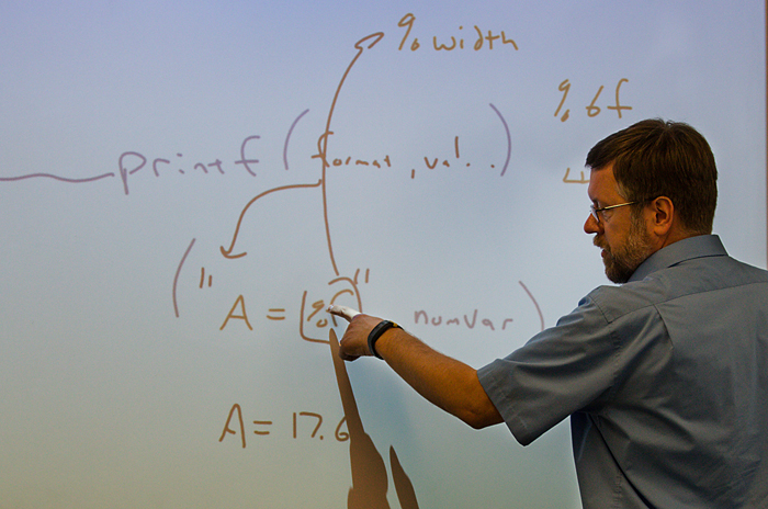 Computer Information Systems professor Alan Collard demonstrates some code on a white board.