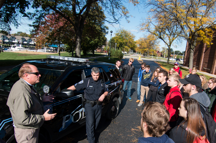 Professor and police officer talk with students.