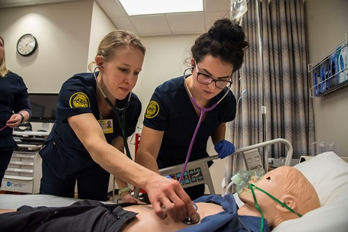 Two nursing students work on a manikin.