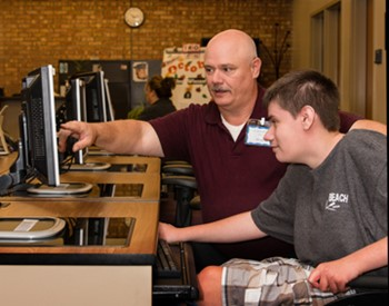 Instructor assists a student with work on a desktop computer.
