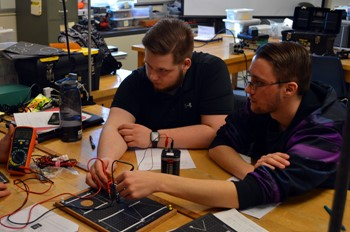 Two students working together on an electronics project.