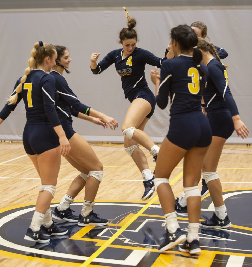 Six volleyball players celebrate a point.