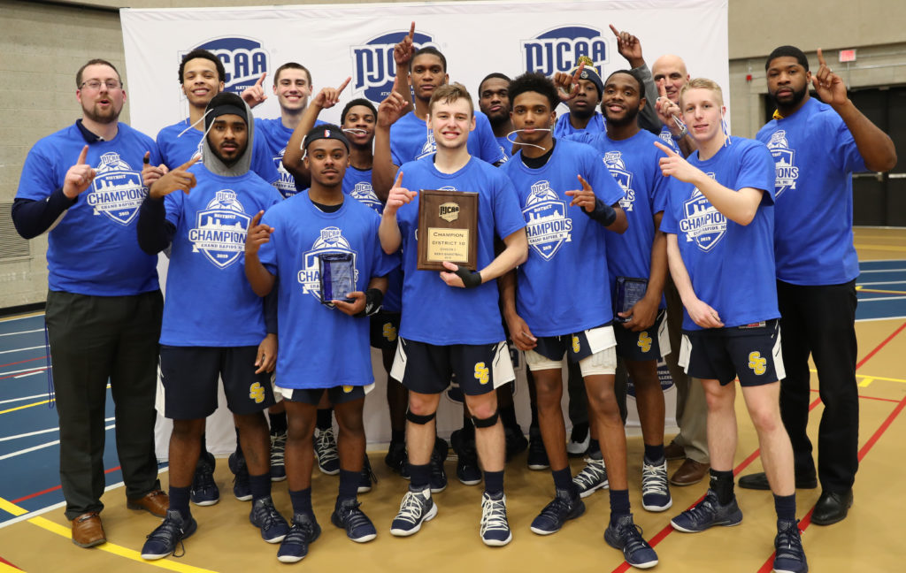 Men's basketball team poses after earning the NJCAA Division II District X Championship.