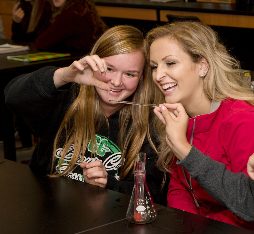 Two SC4 students conduct a science experiment with an eye dropper, beaker and test tube.