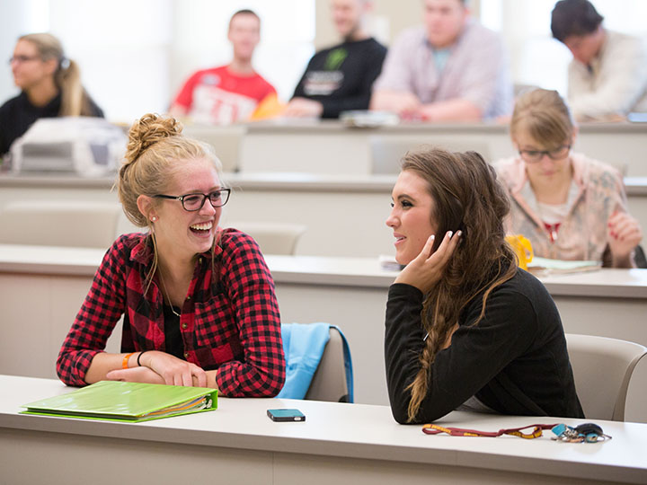 Two female students pictured talking in a lecture hall on campus