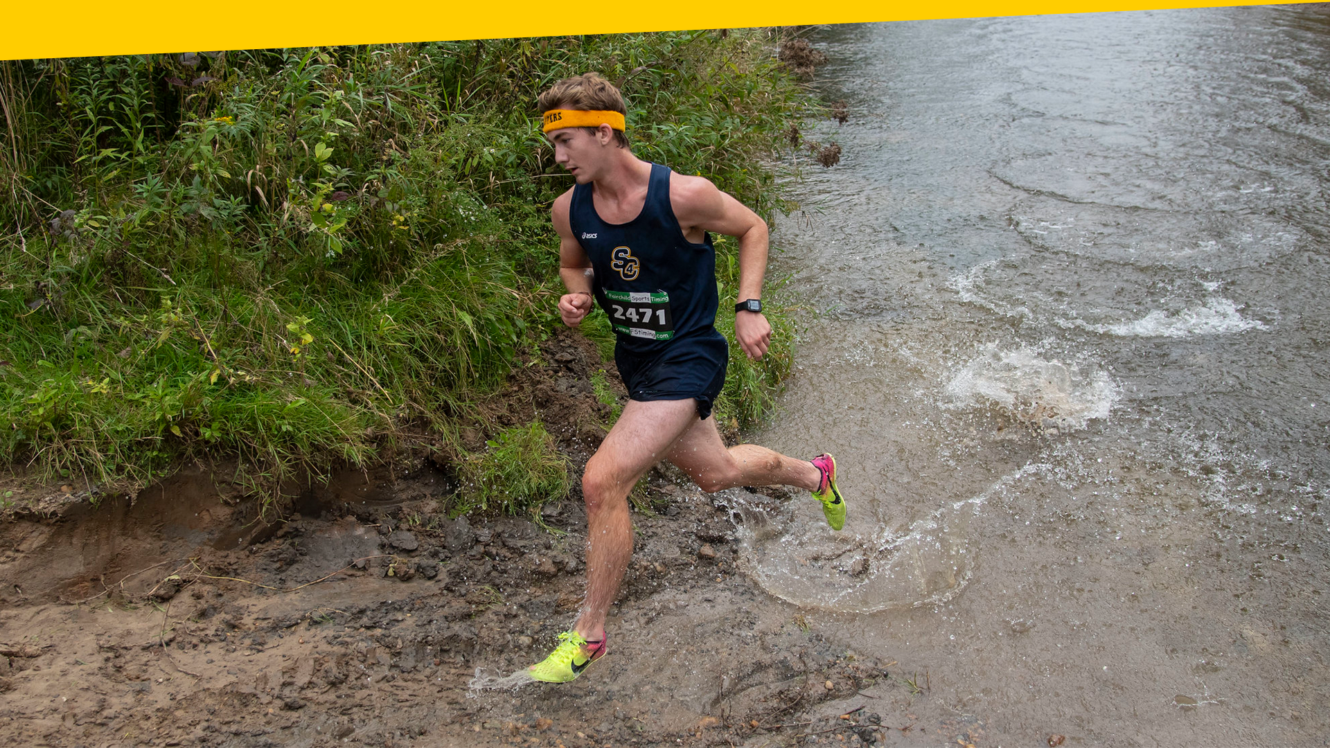 Men's cross country team member runs through water in competition