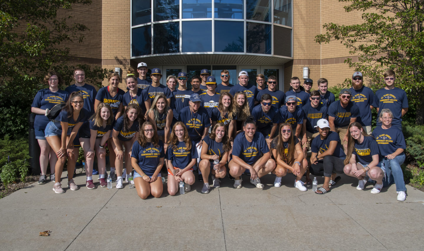 Large group of students pose for picture in front of the Welcome Center