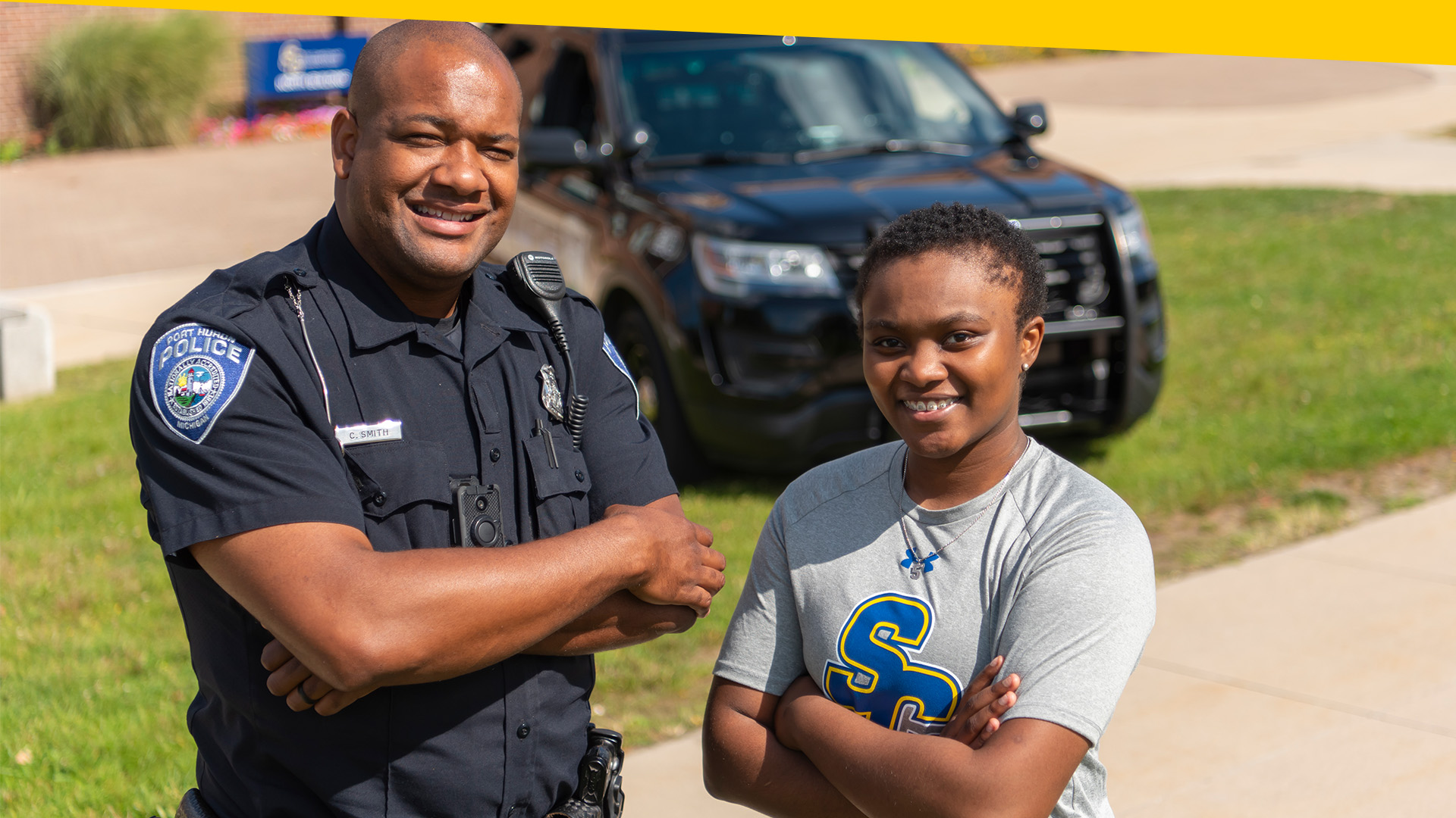 SC4 male officer and female criminal justice student pose in front of police car.