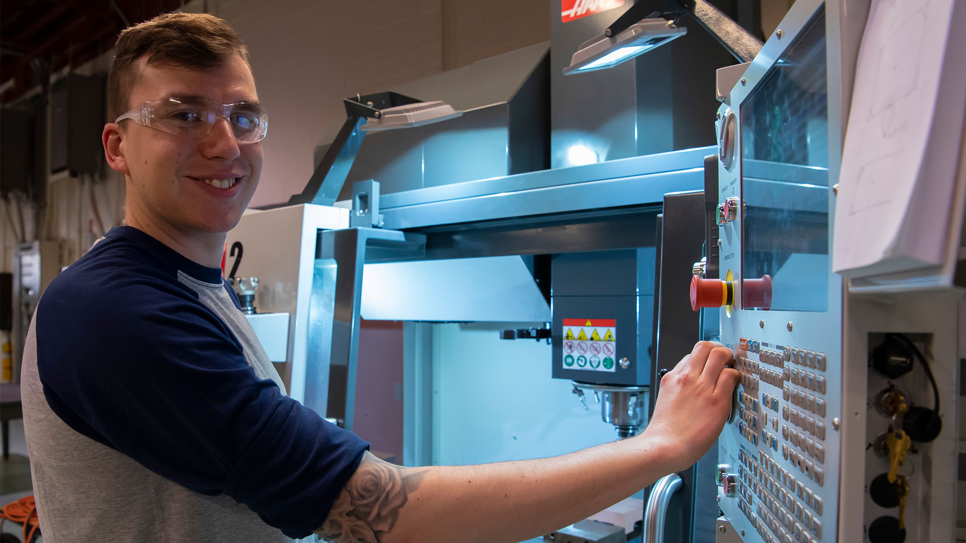 Male student poses for photo in CNC class
