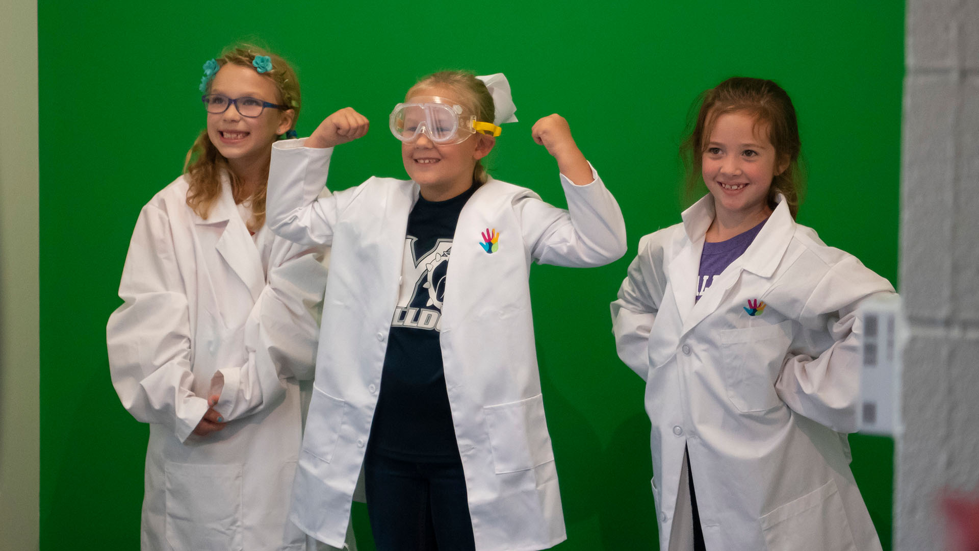 Three female K-12 students pose for photos in Experience Center in lab coats