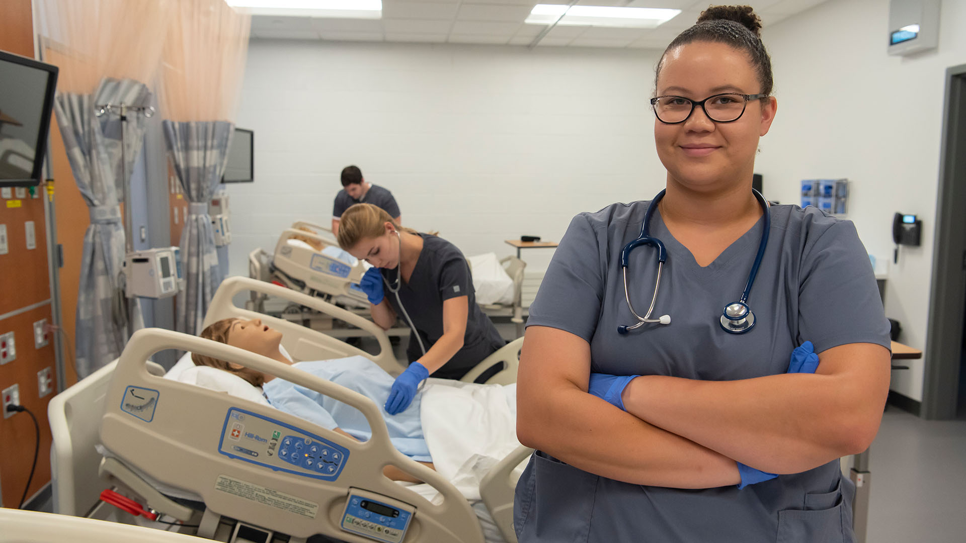 Respiratory therapy student poses in lab in front of manikins and other students