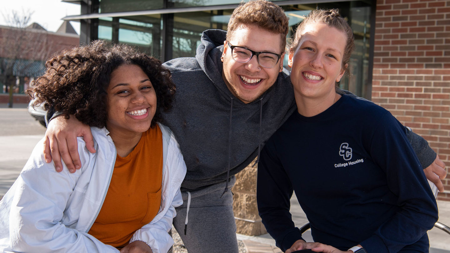 Three students pose for a photo outside of College Housing