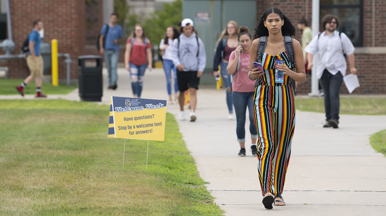 A number of students walk across campus with a welcome week sign in the grass.